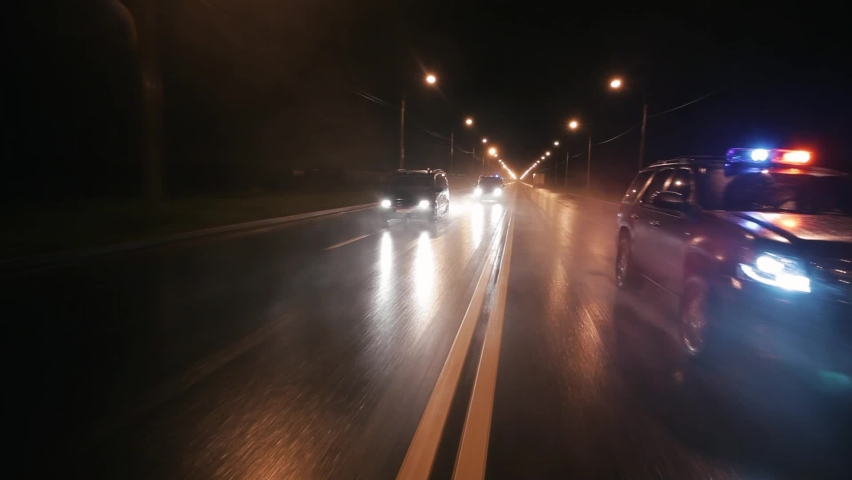 Police cars drive at high speed on the highway at night. It's raining hard. Outdoor front view of police traffic auto driving. Car active driving. Flashers. | Shutterstock HD Video #1058767993