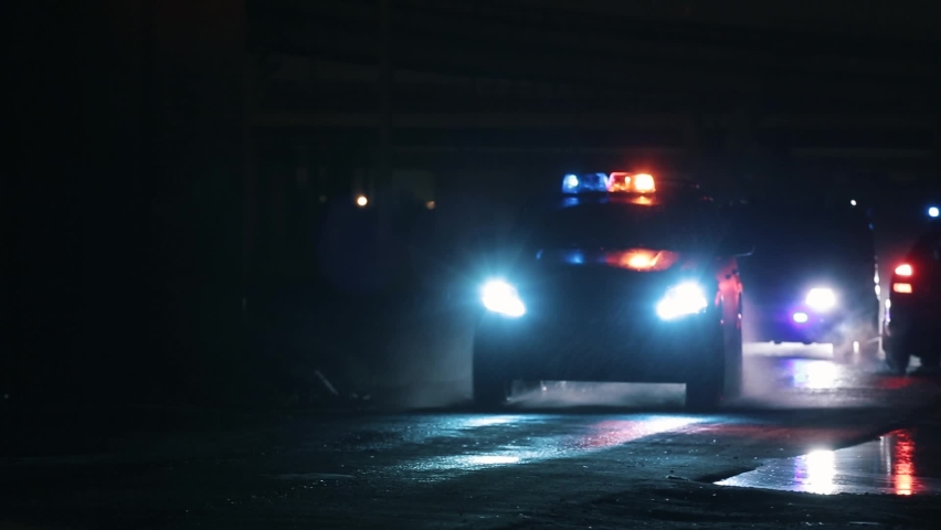 Silhouettes of driving police cars. Flashing lights and glare. It's raining hard. | Shutterstock HD Video #1058768209