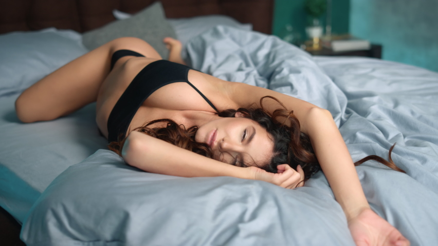 Closeup sexy woman body lying on bed at home. Erotic girl in lingerie looking camera and seductive woman flirting at hotel bedroom. Sensual model opening eyes in bed at home.