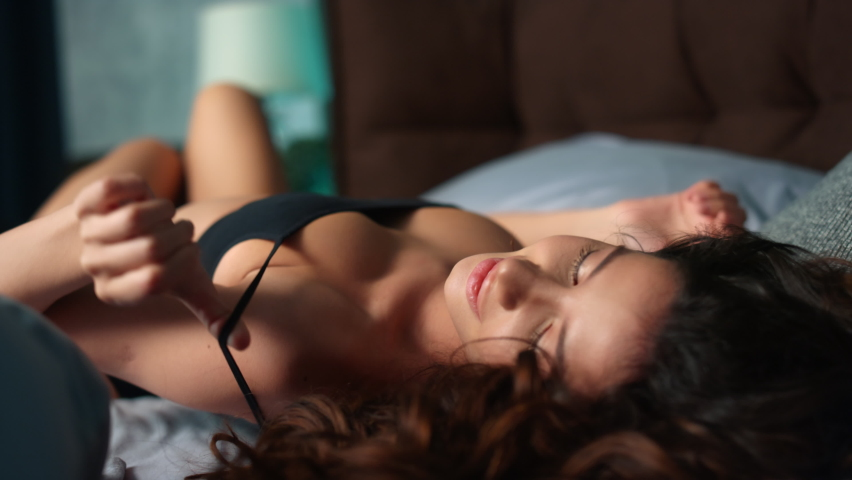 Closeup young sexy woman playing with bra straps in home bedroom. Playful girl model posing in lingerie on bed in slow motion. Erotic woman lying on bed and dreaming about sex indoors.