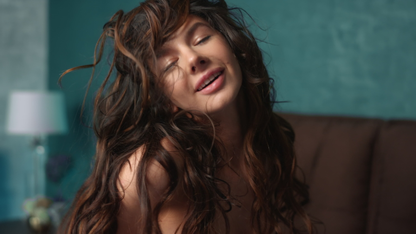 Portrait of pretty woman shaking head with curly long hair in slow motion indoors. Closeup cheerful girl showing beautiful curls for camera. Gorgeous fashion model posing in bedroom.