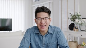 Medium shot ,confident asian creative man vlogger make live video conference call, chat online on computer and sitting on table at home, Webcam view, video chat and Self isolation concept.