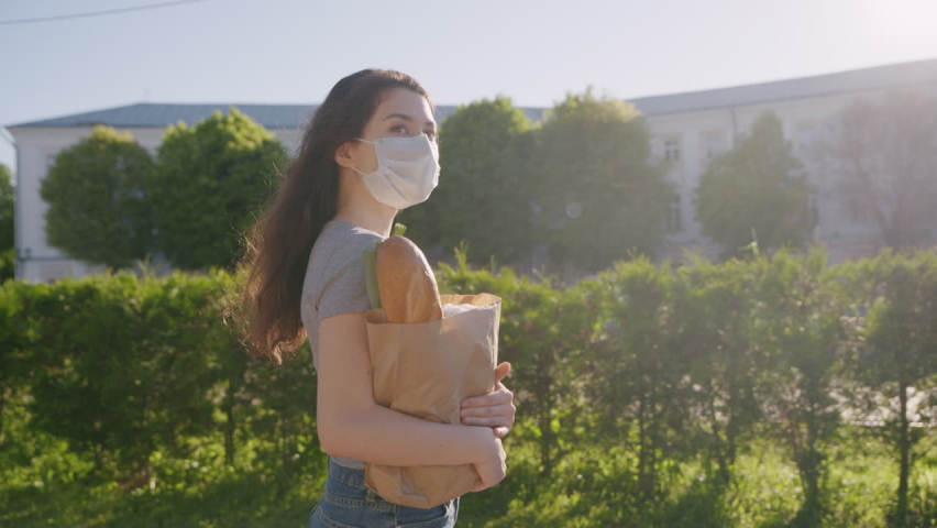 Social distance for prevent outbreak. Pandemic shopping. Young woman in protective mask and gloves carries bag with products from store to home. Another life after quarantine. Covid effect concept. | Shutterstock HD Video #1058780554