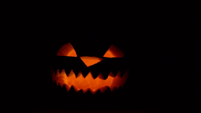 Jack lantern halloween pumpkin face glowing in dark, scary horror atmosphere, pumpkin with candle, tradition autumn holiday decor | Shutterstock HD Video #1058785165