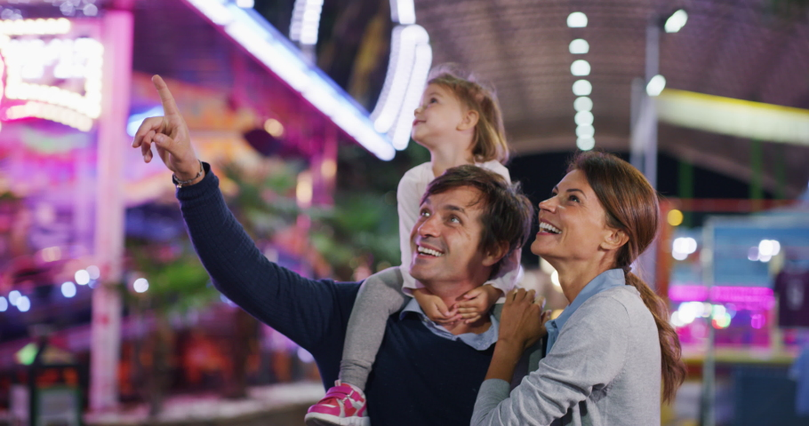 Authentic shot of a happy smiling family is having fun together in amusement park with luna park lights at night. Royalty-Free Stock Footage #1058790043