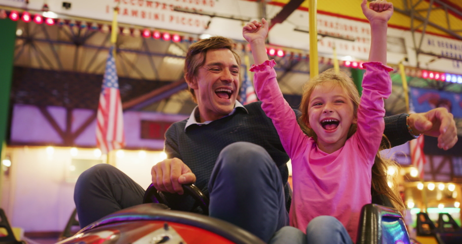 Authentic shot of a happy smiling father and little daughter are having fun to drive a bumper car together at fun fair in amusement park with luna park lights at night. Royalty-Free Stock Footage #1058792251
