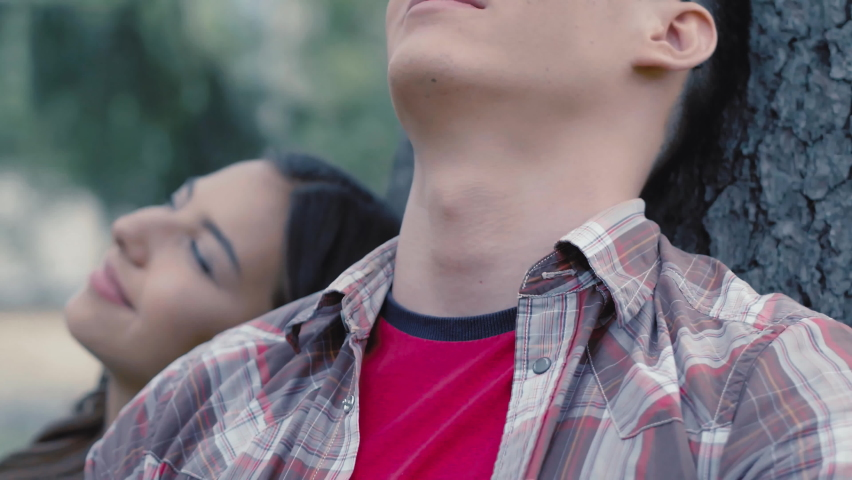 Fellow student is resting in a park under a tree. A student with glasses. Rest on the break. High quality 4k footage.