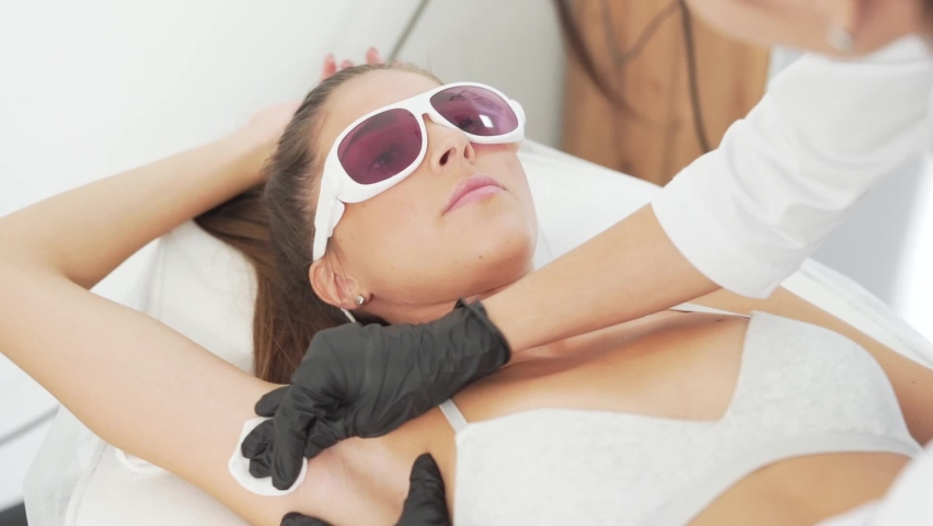 Preparation for the armpit hair real procedure the doctor applies a special cream. | Shutterstock HD Video #1058806045