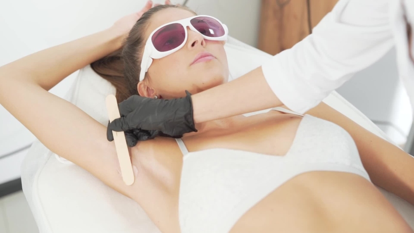 Preparation for the armpit hair ral procedure, the doctor applies a special cream | Shutterstock HD Video #1058806591