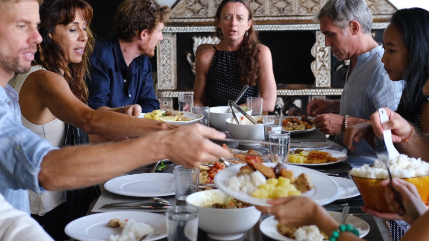Diverse group of multiethnic friends enjoying meal sharing and passing food to each other in outdoor cafe or home. Leisure, food and drinks, people and holidays concept Royalty-Free Stock Footage #1058808628