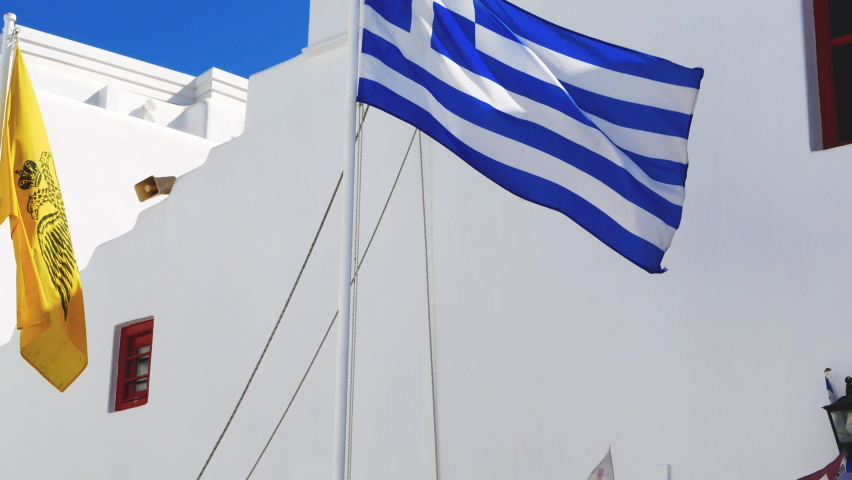Bottom view of an Orthodox church in Mykonos against blue sky with waving Greek flag and other colorful pennants   Shutterstock HD Video #1058810683