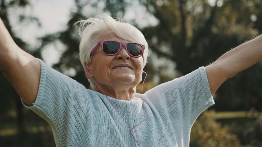 Senior retired woman enjoying the freedom of retirement. Outstretched hands in the park, close up. High quality 4k footage | Shutterstock HD Video #1058812690