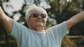 Senior retired woman enjoying the freedom of retirement. Outstretched hands in the park, close up. High quality 4k footage