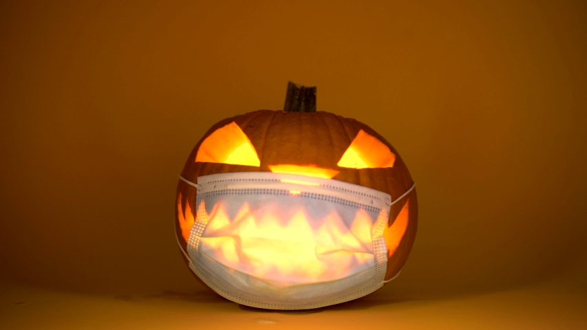 Carved Halloween pumpkin glowing with protective medical mask on face, coronavirus and quarantine concept, covid-19 halloween party costume. With intentional added grain for artistic purposes. | Shutterstock HD Video #1058813293