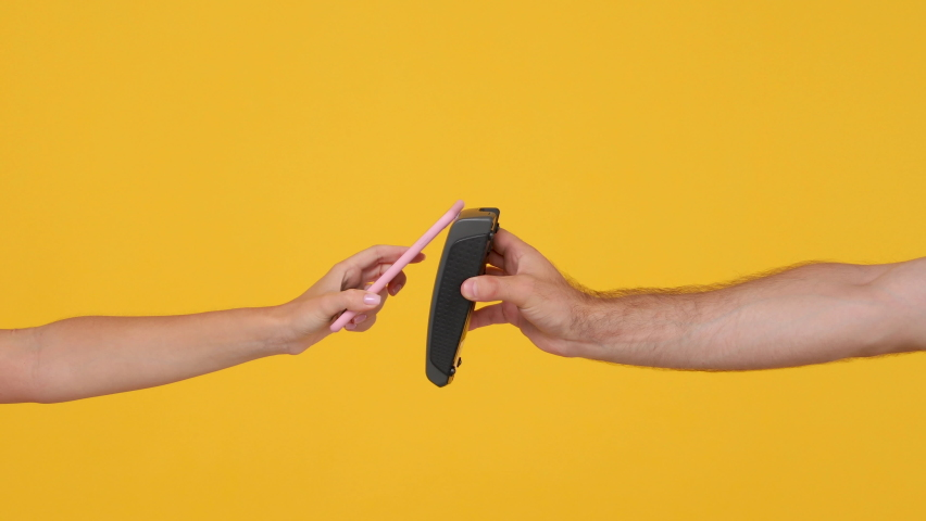Close up cropped of man hold in hand wireless modern bank payment terminal to process acquire credit card payments woman pay use smart mobile phone isolated on yellow background. Mock up advertising Royalty-Free Stock Footage #1058814868