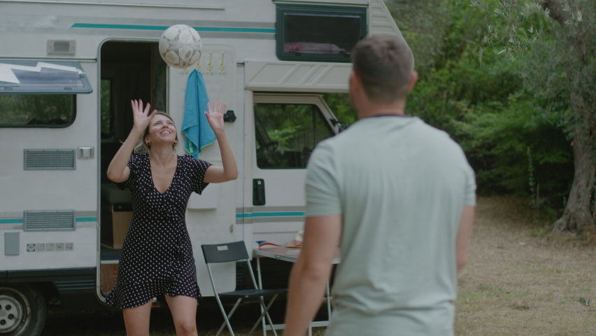 Pretty couple play volleyball together in nature enjoyng vacation near motor home RV campervan. Traveling in recreational vehicle.  | Shutterstock HD Video #1058817784