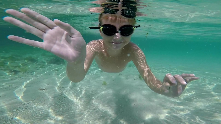 Underwater shot of a cute little boy snorkeling with swimming goggles in a tropical sea