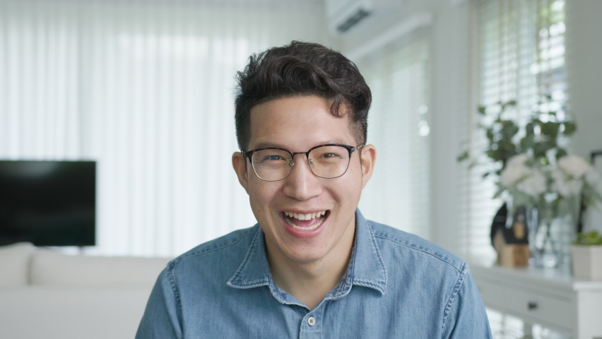 POV screen camera shot ,confident asian creative man vlogger make live video conference call, chat online on computer and sitting on table at home, Webcam view, video chat and Self isolation concept. Royalty-Free Stock Footage #1058821147