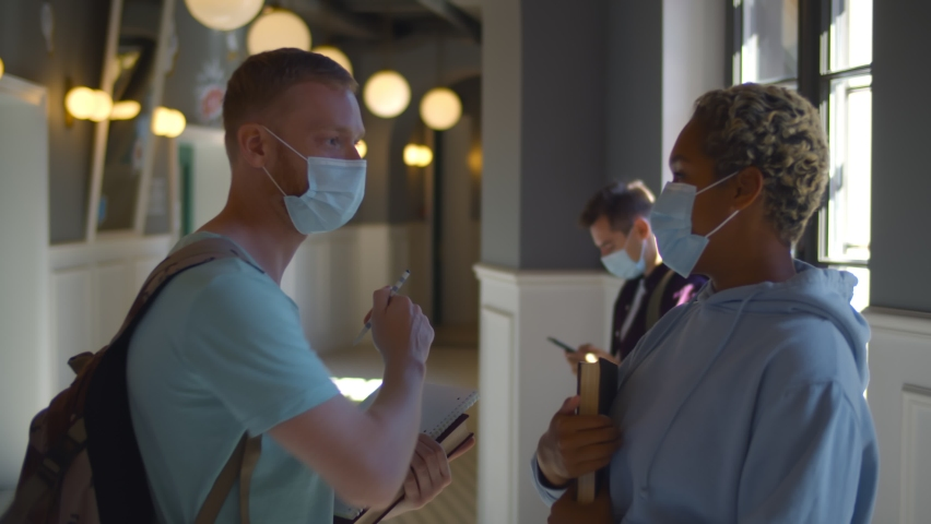Young college friends wearing face mask doing new social distancing greet with elbows bumps. Diverse students in safety mask meeting in college corridor Royalty-Free Stock Footage #1058822656