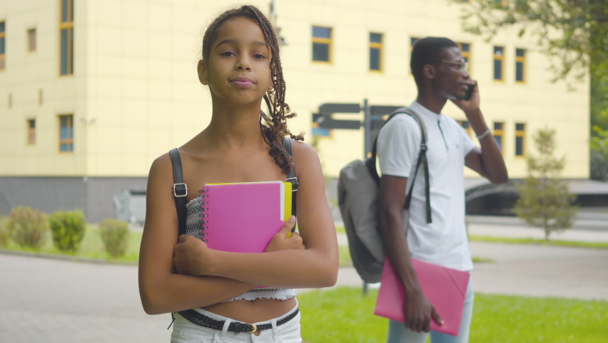 Portrait of charming African American schoolgirl posing outdoors with her busy brother talking on the phone at the background. Smiling pretty girl standing on college yard with workbook and backpack. Royalty-Free Stock Footage #1058823901