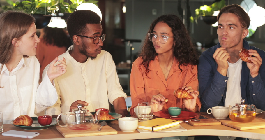 Millennial friends enjoing delicious croissants while sitting in modern cafe. Group of young people eating food while spending good time together after work. Concept of eat out | Shutterstock HD Video #1058826700