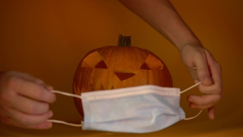 Halloween carved glowing pumpkin with medical mask, put protective mask on quarantine, coronavirus halloween 2020 | Shutterstock HD Video #1058832802