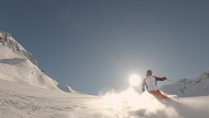 Skier skiing on ideal ski slope in big mountains on sunny day behind camera. Winter outdoor activities. Slow motion, 2K RAW footage, 2704x1520