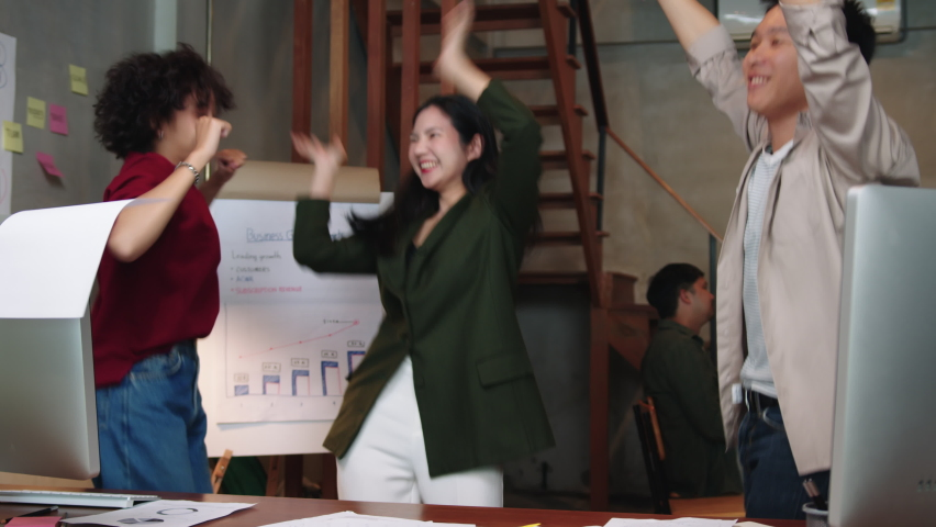Group of Asian Business people have fun dancing, throwing paper documents celebrating a successful business project in loft creative office. Business team enjoying victory and success at the workplace