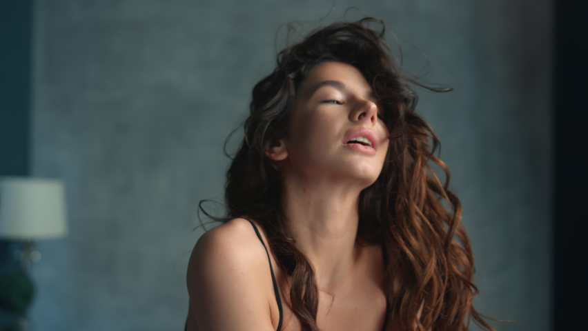 Portrait of hot woman touching hair in bedroom in slow motion. Closeup sensual girl relaxing at home. Young fashion model smiling camera indoors.