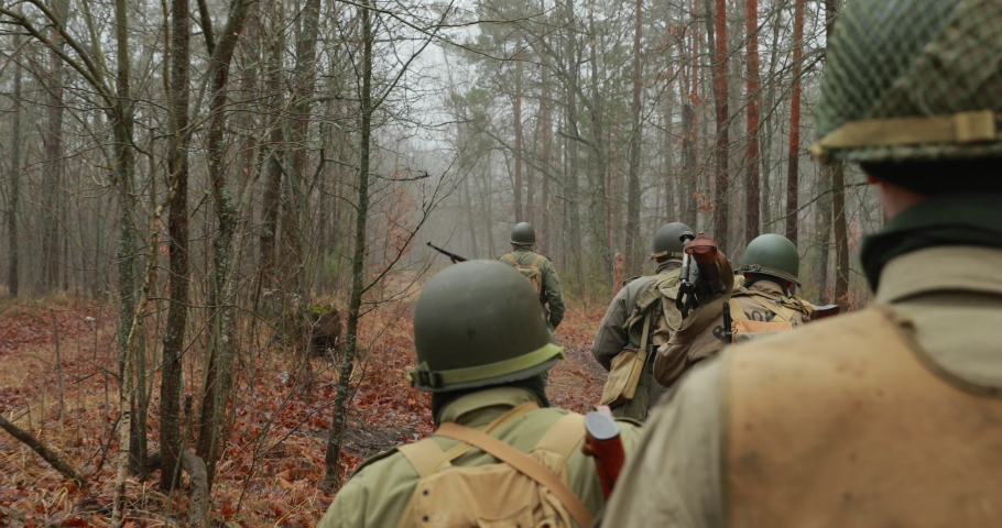 Historical Re-enactment. Re-enactors Dressed As American Soldiers Of USA Infantry Of World War II Marching Walking Along Forest Road In Autumn Day. Group of Soldiers Marching In Forest.