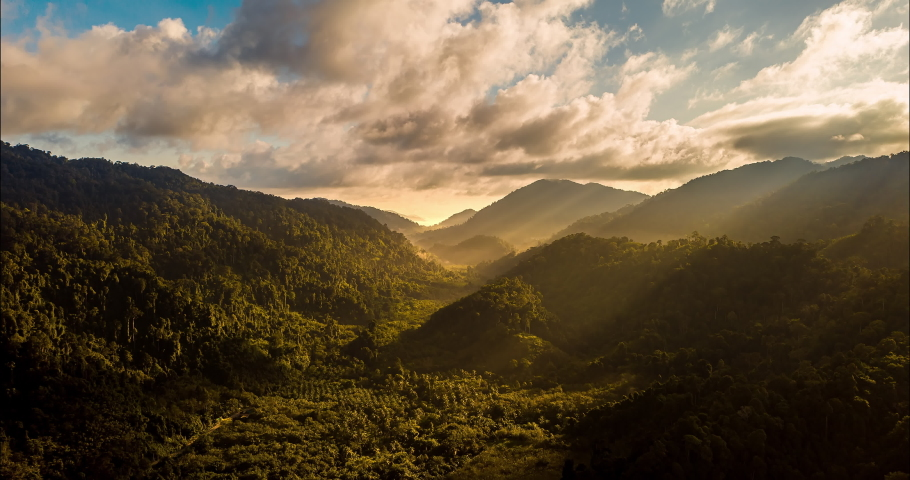 Aerial drone hyperlapse timelapse of beautiful tropical valley between mountains. The first rays of the rising sun break through the clouds and clouds. The last rays of the sunset hit the tree crowns.