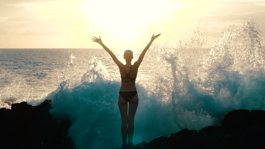 Silhouette woman at sunset raising arms in air and observing ocean waves crashing on rocks and spraying. Concept of explosion of emotions, joy, happiness in life. Traveling around world, slow motion.
