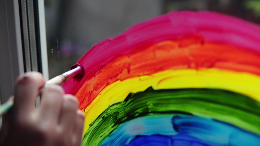 Painting a rainbow with paints on a window close-up | Shutterstock HD Video #1058851645