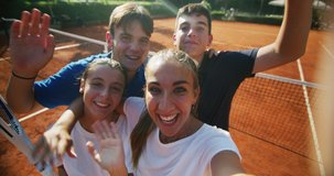 Authentic shot of young happy teenage tennis players friends having fun to make selfie or video call to friends or family after a friendly match or training workout game on the court in a sunny day.