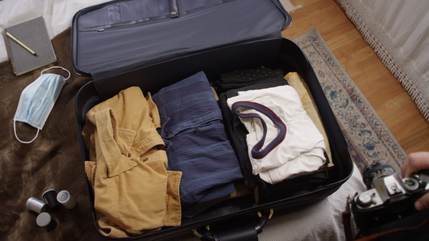 Man puts his camera, film, and notebooks into a neatly packed suitcase for a vacation   Shutterstock HD Video #1058854201