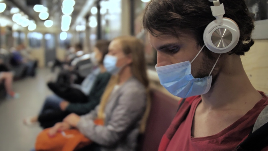 Side view of young brunette male wearing protective mask and listening to music in headphones while sitting in underground subway during covid-19 outbreak, lockdown, public caution, social distancing Royalty-Free Stock Footage #1058854594