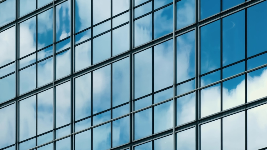 Time lapse of blue sky and clouds reflected in structural modular glass wall.  | Shutterstock HD Video #1058856853