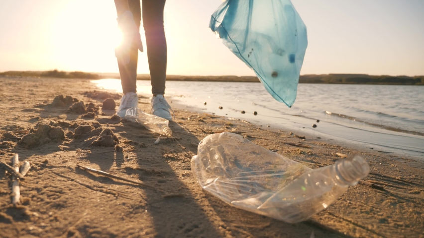 Teamwork cleaning plastic on the beach. Volunteers collect trash in a trash bag. Plastic pollution and environmental problem concept. Voluntary cleaning of nature from plastic. Greening the planet | Shutterstock HD Video #1058858656