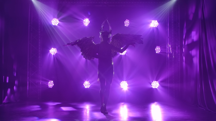 A beautiful woman actress in a costume of the Greek goddess Artemis with wings dances. Silhouette on a purple background in the studio. Slow motion. | Shutterstock HD Video #1058858761