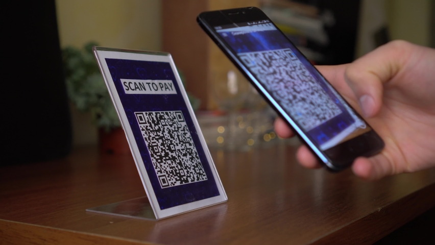 Safely buying and selling touch free. Contactless QR Code Commerce. A man scans the QR code displayed by the merchant with their phone to pay for service Royalty-Free Stock Footage #1058859586