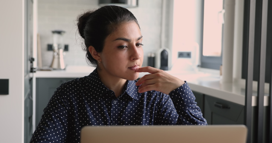 Young indian woman sit in homeoffice working on laptop doing remote freelance tasks looking pensive or concerned, thinking of problems, solving business issues. Creative telework, brainwork concept Royalty-Free Stock Footage #1058862400