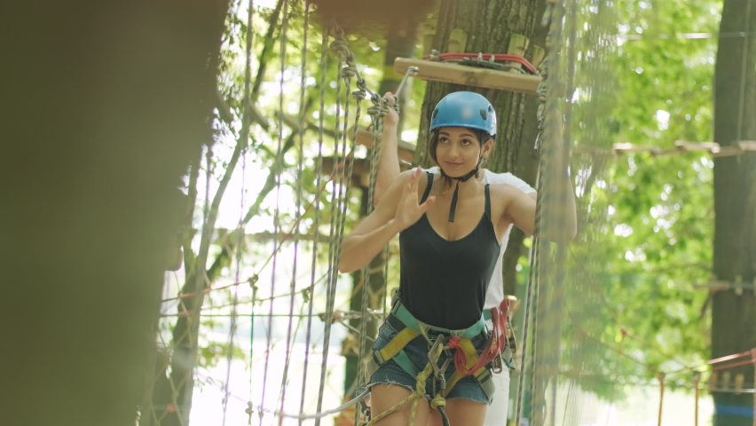 Adventure climbing high wire park - people on course in mountain helmet and safety equipment   Shutterstock HD Video #1058862658