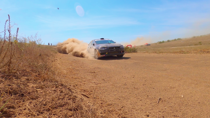 Rally car driving fast in cross-country road. Fast car is going with dust. Speed off-road riding on dusty road. Royalty-Free Stock Footage #1058866378