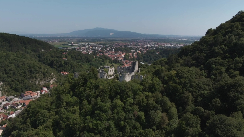 Pivot Aerial shot around the castle of Samobor over a green hill with the city of Samobor in the background.