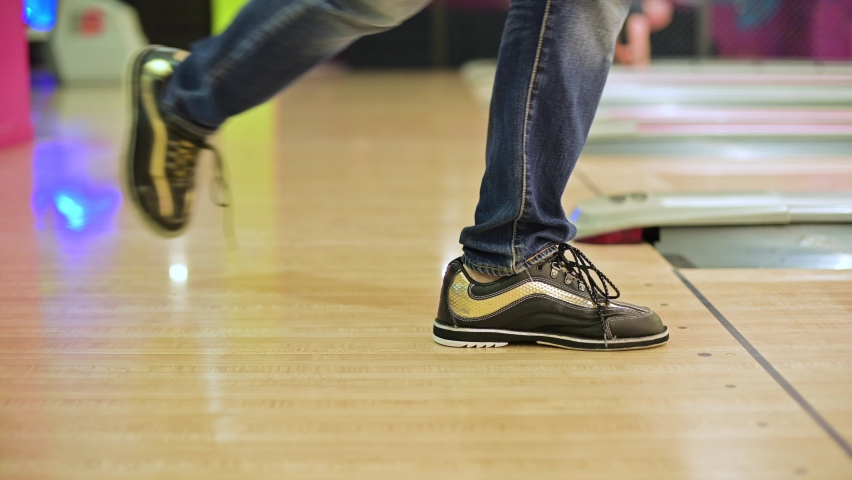 The bowling player's feet slide abruptly and stop abruptly before the start of the track. The game threw a bowling ball