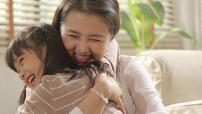 Happy little Asian Cute Girl hugging, embracing her mom enjoying, bonding, and laughing together. Mother parent hugging her kid having a tender and lovely moment in living room at home Royalty-Free Stock Footage #1058888410