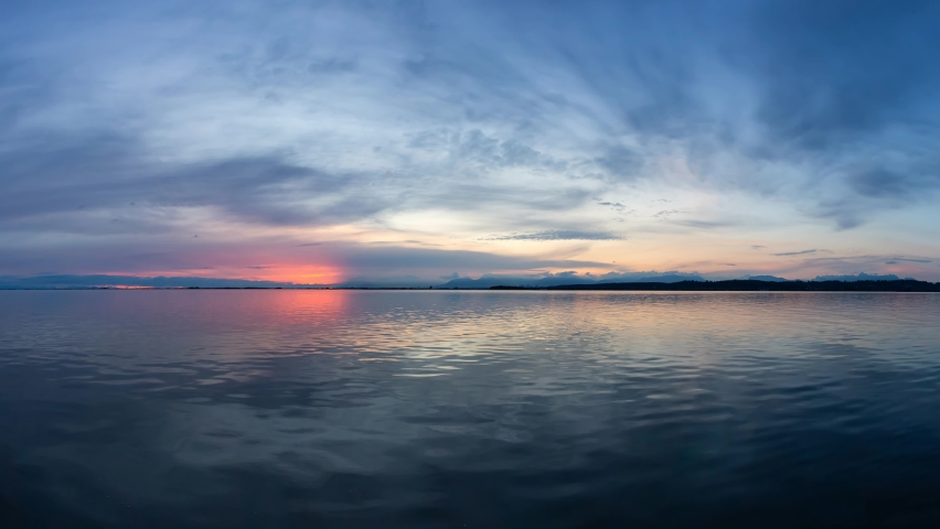 Cinemagraph Continuous Loop Animation. View of the Calm Water on the Pacific Ocean Coast during a colorful cloudy sunset. Taken in White Rock, Vancouver, British Columbia, Canada. Royalty-Free Stock Footage #1058891440