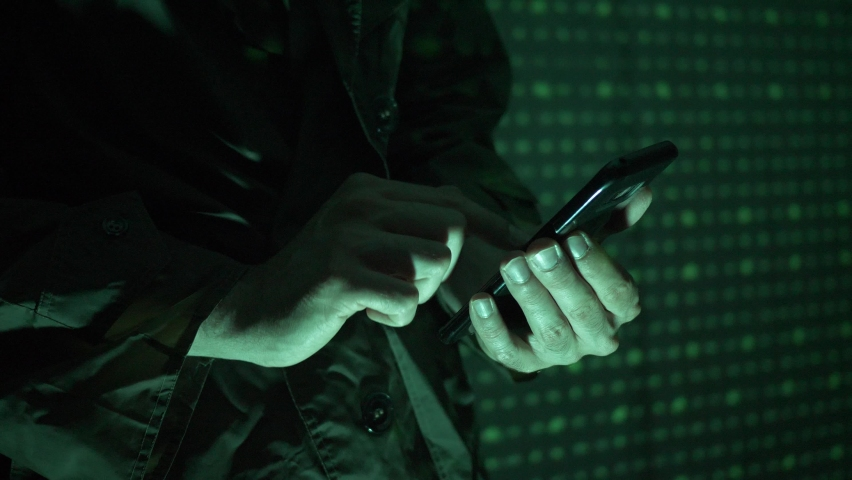 Hacker using a mobile phone to hack the system. He is standing in the dark with a matrix-like background. Royalty-Free Stock Footage #1058892640