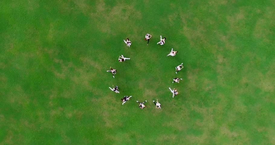 A group of young dancers dancing bachata on a large green lawn. The dancers are lined up in a circle and spinning. The guys are holding the girls in their arms. Aerial view. 4K Footage