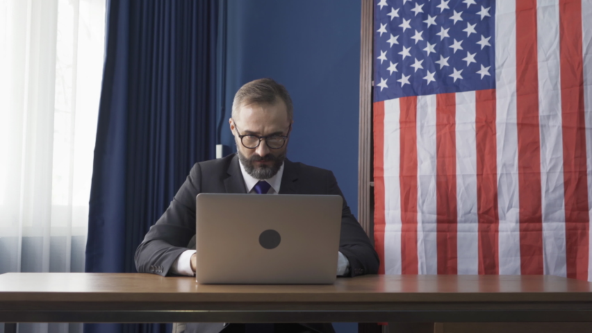 Smiling business vintage, white gentleman, Caucasian person with american or usa national flag working from home on table with computer notebook laptop on webcam video call conference in quarantine.
